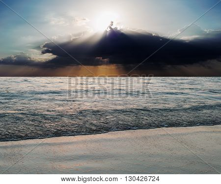 Sea and beach storm with sun ray and over dark tone