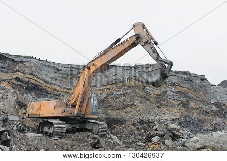 Excavator works in career in a rainy day.