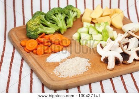 Fresh sliced soup ingredients laids on wooden cutting board. Top-side view low aperture shot