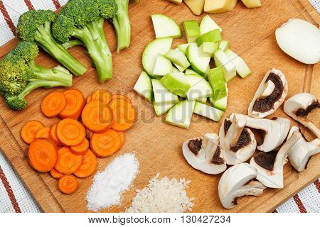 Sliced vegetables an spice laids on wooden cutting board. Top view