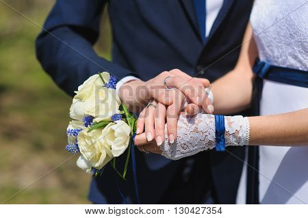 Groom and the bride with a bouquet of roses. Bride with groom holding wedding bouquet at ceremony.