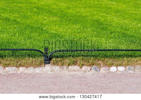 green lawn with a protection and part of a walking path in park or in the square for a natural background