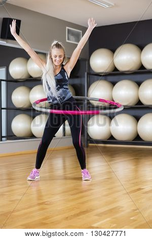 Woman Exercising With Hula Hoop In Gym