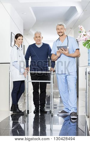 Portrait Of Physiotherapists And Senior Patient In Rehab Center