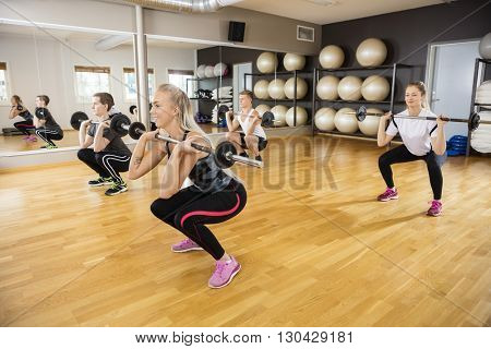Friends Lifting Barbells In Fitness Club