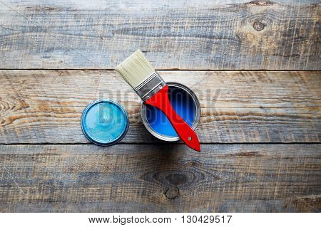 open jar with blue paint and brush  with red grip on the wooden background top view close up