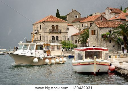 PERAST MONTENEGRO - May 15 2016: Perast city in Kotor bay with beautiful mountains and boat floating in Montenegro