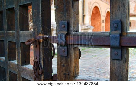 Iron locking bar with a chain on old wooden gate