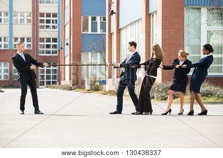 Male And Female Businesspeople Playing Tug Of War Against One Businessman