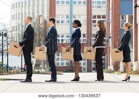 Group Of Multiracial Businesspeople With Cardboard Boxes Standing In A Line