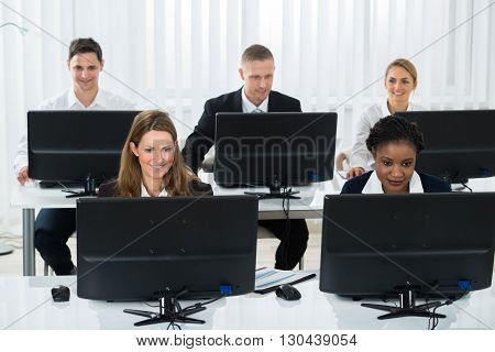 Happy Group Of Businesspeople Working On Computers In Office