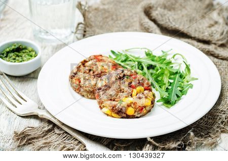 green lentils corn pepper fritters on white wood background
