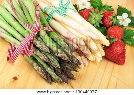 Green white asparagus with fresh strawberries on bright wood. Healthy cooking concept.