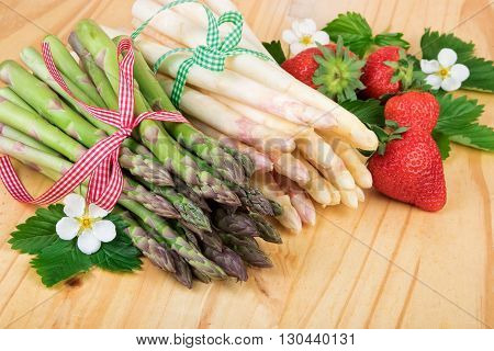 Bundle of fresh asparagus with strawberries on wood. Vegan food vegetarian and healthy cooking concept.