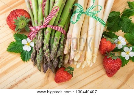 Green and white asparagus decorated in retro style on wooden background.Top view.