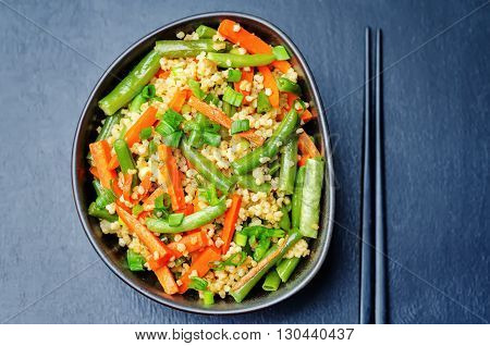 Millet carrots green beans Stir-Fry on a dark background