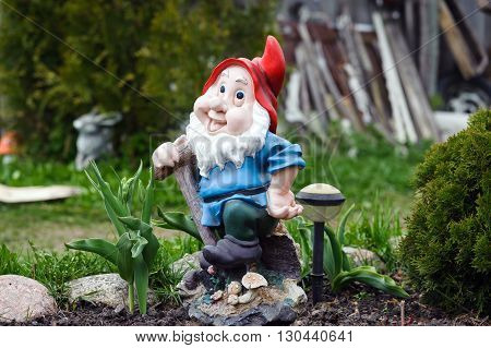 DAUGAVPILS, LATVIA - MAY 2, 2016: Statue of gnome with red hat in garden