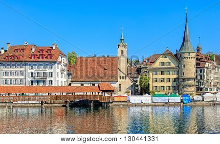 Lucerne, Switzerland - 7 May, 2016: view on the Reuss river with the St. Peter's Chapel and the Chapel Bridge. Lucerne is a city in central Switzerland, it is the capital of the Swiss Canton of Lucerne and the capital of the district of the same name