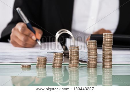 Close-up Of Businesswoman Calculating Tax With Stack Of Coins On Desk