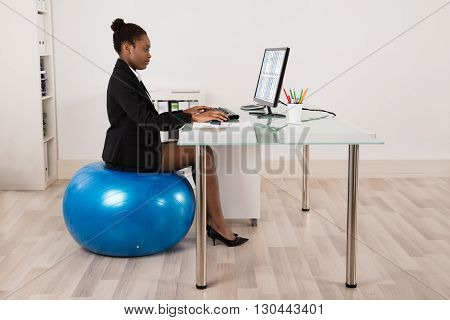 Young African Businesswoman Using Computer While Sitting On Fitness Ball In Office
