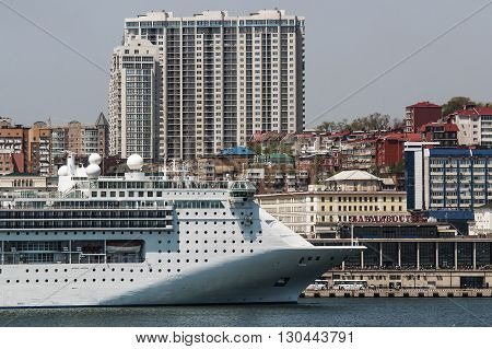 white cruise liner on a background of city buildings
