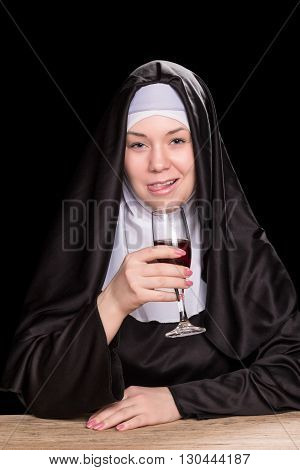 Nun tongue out while sitting at a wooden table with a glass of wine in hand isolated on a black background