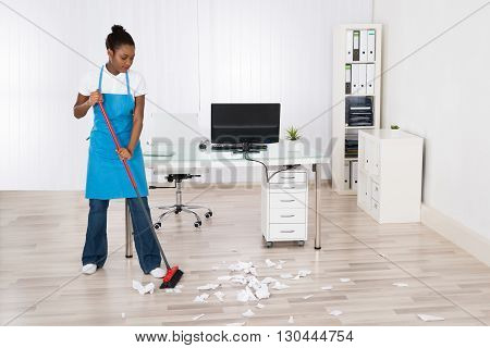 Young Female Janitor Sweeping Torn Paper Pieces On Hardwood Floor