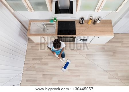 High Angle View Of Young Female Janitor Cleaning Floor In Kitchen