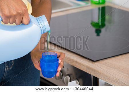Close-up Of A Woman's Hand Pouring Detergent In The Blue Bottle Cap