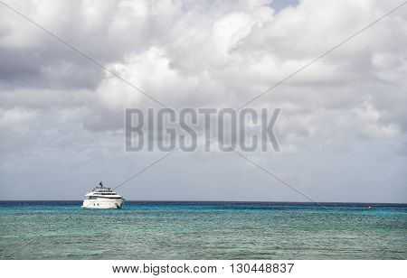 Yacht on water and grey cloudy sky in moody weather outdoor on horizon line background copy space