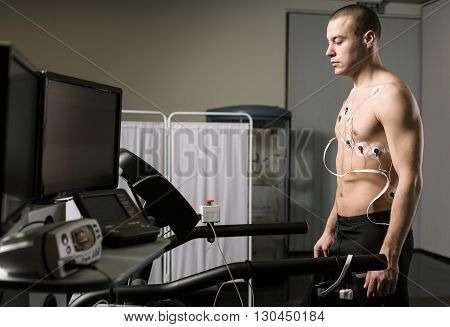 Sportsman is standing on a treadmill and preparing for a medical trial