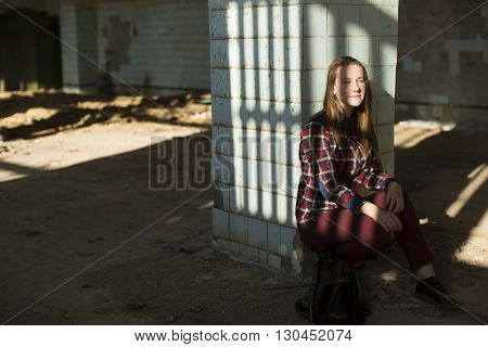 Teen girl sitting in an abandoned building in the rays of light.