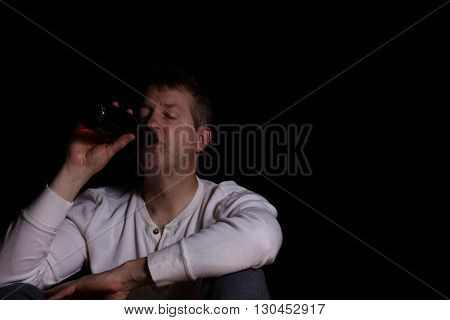 Depressed man drinking beer out of a bottle while sitting down in a dark background.