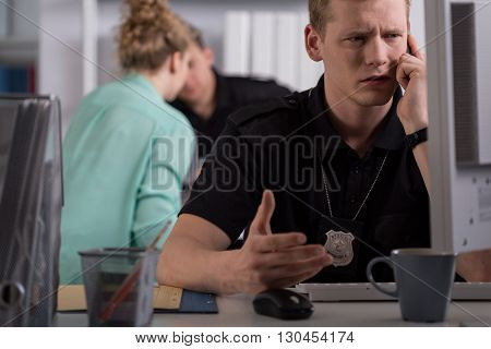 Shot of a young police officer talking on the phone at a police station