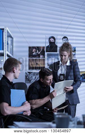 Shot of three police officers reading files at a police station