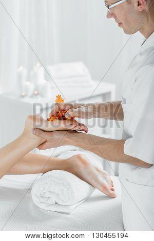 Professional masseur massaging woman's feet light interior