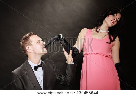Date. Gallant man in suit and woman in evening dress on black grey background in studio.
