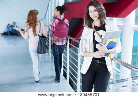 High school student with notes standing in school hall
