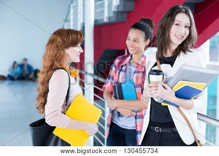 Smiling students talking and drinking coffee in school hall