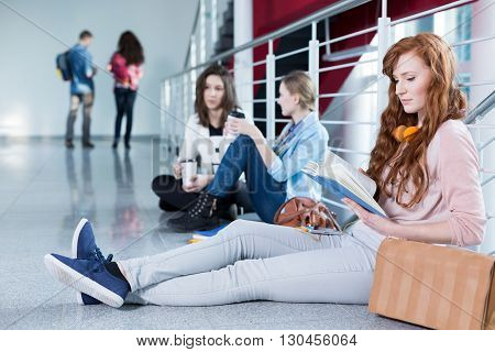 Female student sitting on the floor and reading notes before exam