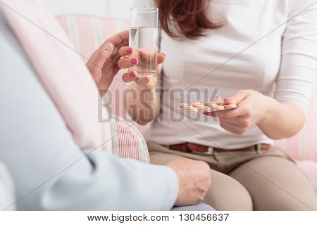 Woman giving medicines and glass of water to elderly person