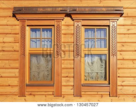 wooden windows in wooden panneled house wall