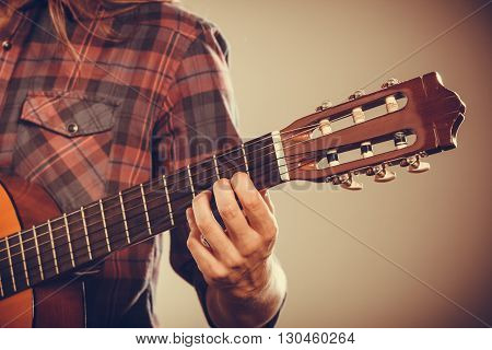 Musicans arm holding strings. Guitar with part of guitarist. Sound instrument music passion hobby concept.