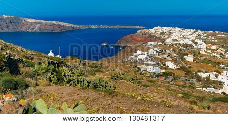 Aerial panoramic view of Oia or Ia and Finikia on the island Santorini, white houses, windmills and church with blue domes, Greece