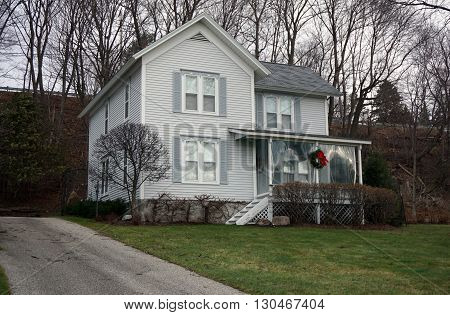HARBOR SPRINGS, MICHIGAN / UNITED STATES - DECEMBER 24, 2015: A white home below the bluff on Fourth Street in Harbor Springs, Michigan.