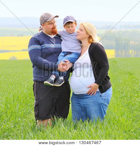 Young farmer's family together on green wheat field. Pregnant mother and overweight father with their little son. People working and enjoying life on countryside. Woman, man and child.