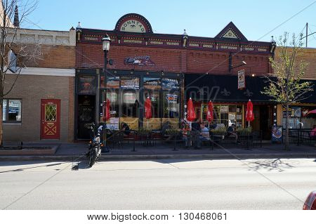 PLAINFIELD, ILLINOIS / UNITED STATES - SEPTEMBER 20, 2015: People enjoy sidewalk dining at Moe Joe's Restaurant, in the historic Sonntag Building in downtown Plainfield.