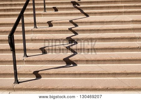 Wide limestone staircase with iron railing and clear shadow