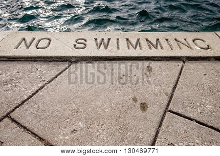 Concrete walkway next to a river, with a no swimming sign