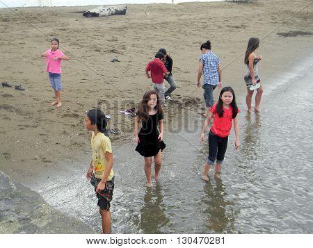 CEBU CITY, CEBU / PHILIPPINES - JULY 30, 2011: Children wade in the water at a beach in Cebu.